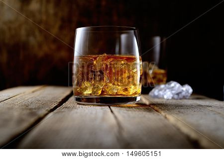 whiskey with ice on a wooden background