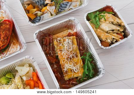 Healthy food delivery, daily ration. Take away of natural organic low carb diet. Fitness nutrition in foil boxes. Top view, flat lay with copy space at white wood. Lasagna, vegetables and fruits