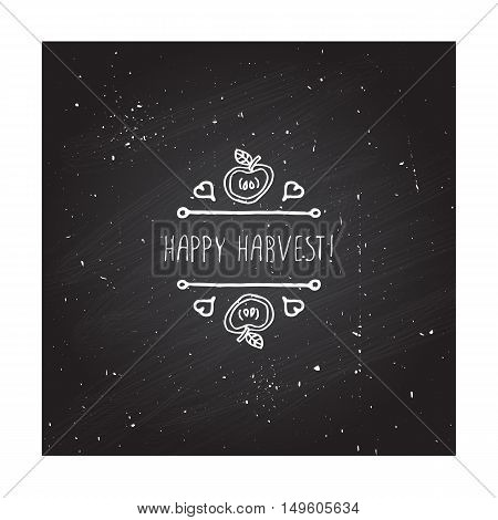 Hand-sketched typographic element with apple, hearts and text on blackboard background. Happy Harvest