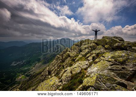 Mountain landscape and self portrait from hill Chopok in Low Tatras at Slovakia. Dramatic cloudy sky during summer day at mountain peak.
