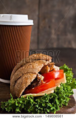 Grain Croissant Sandwich And A Cardboard Cup Of Coffee On A Dark Background