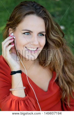 Cool woman in a park in summer smiling and listening to music on the headphones