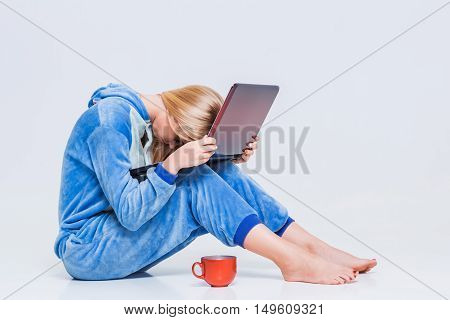 girl in pajamas with a laptop lying on the floor. studying or doing online shopping. work from home. tired woman, it does not work