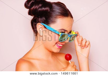 Bright skin young girl with sunglasses and lollipop