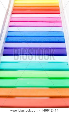 Bunch of square colorful pastel chalks vertical closeup shot with depth of field