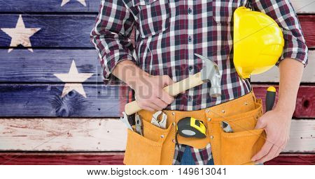 Repairman with hard hat and hammer against composite image of usa national flag