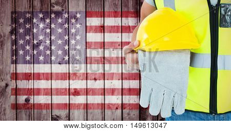 Construction worker holding gloves and hardhat against composite image of usa national flag