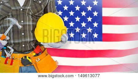 Manual worker wearing tool belt while holding hammer and helmet against rippled us flag