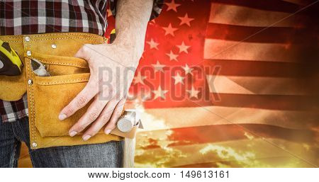 Handyman wearing tool belt against american flag rippling against sunrise over mountains