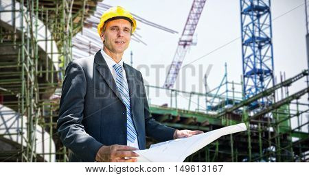 Portrait of smiling architect holding blueprint against work in progress in the city
