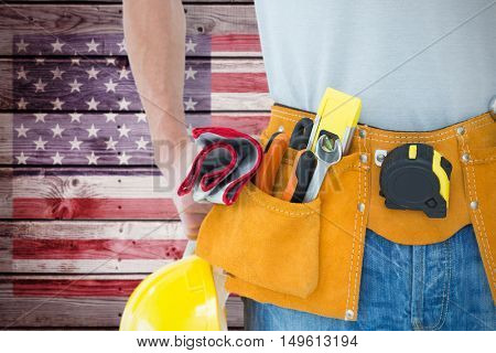 Technician with tool belt around waist against composite image of usa national flag