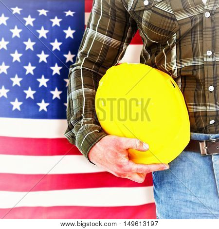 Manual worker holding helmet against rippled us flag