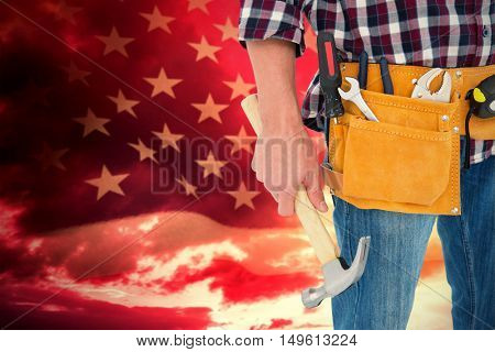 Repairman wearing tool belt while holding hammer against american flag rippling over grassy landscape