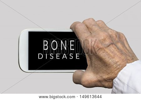 Smart phone in old hand with BONE DISEASE text on screen. Selective focus