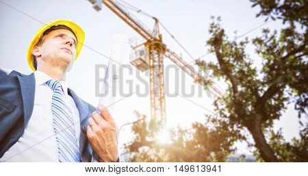 Low angle view of architect holding blueprint against view of a crane