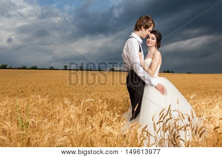 Young Bride And Groom Posing In Wheat Field With Dramatic Sky In The Back