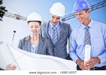 Businessmen and a woman with hard hats and holding blueprint against crane and building construction site