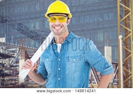 Architect holding rolled blueprint against construction site