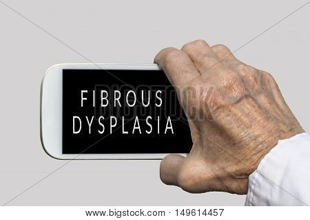 Smart phone in old hand with FIBROUS DYSPLASIA text on screen. Selective focus