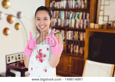 Woman wearing rubber gloves giving thumbs up against view of studio