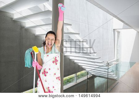 Woman holding a sponge in the air and shouting against stylish modern home interior with staircase