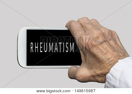 Smart phone in old hand with RHEUMATISM text on screen. Selective focus