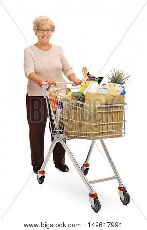 Full length portrait of a joyful mature woman posing with a shopping cart full of groceries isolated on white background