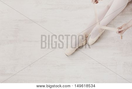 Closeup of young ballerina legs, puts on pointe shoes at white wooden floor background, top view from above with copy space. Ballet practice. Beautiful slim graceful feet of ballet dancer.