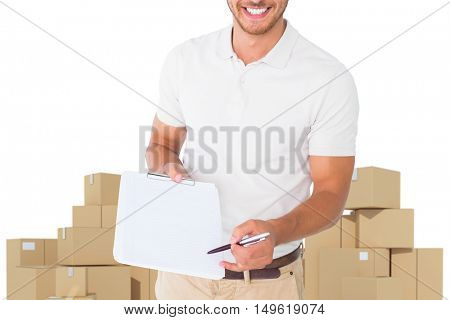 Happy delivery man holding clipboard against cardboard boxes over white background