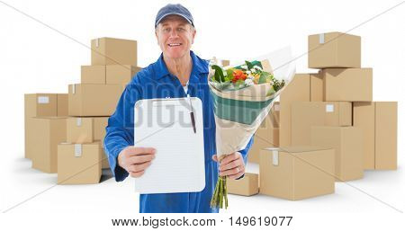 Happy flower delivery man showing clipboard against cardboard boxes over white background