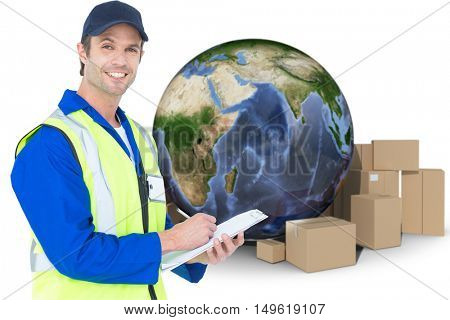 Handsome supervisor writing notes on clipboard against globe amidst cardboard over white background
