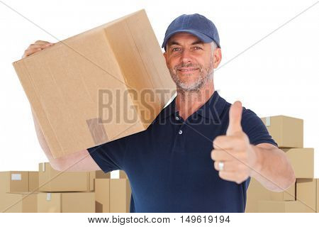 Happy delivery man holding cardboard box showing thumbs up against cardboard boxes over white background
