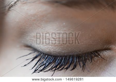 Macro shot of beautiful woman eye closed with long eyelashes