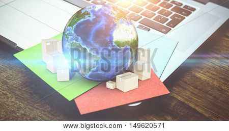 Globe and cardboard boxes against high angle view of sticky notes on laptop