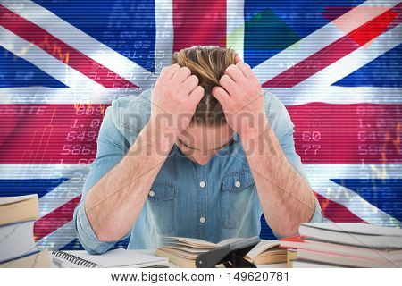 Frustrated man with hand in hair while sitting at desk against digitally generated uk national flag