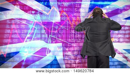Stressed businessman with hands on head against digitally generated great britain national flag