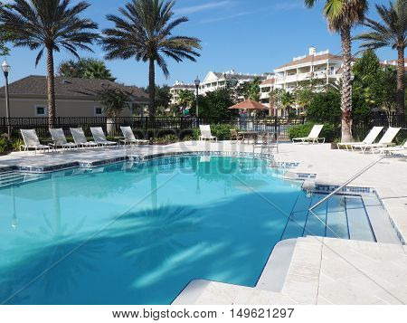 large inground swimming pool at a tropical resort. There are lounge chairs around the pool but no people.