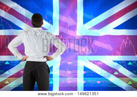Businessman standing back to the camera with hands on hips against digitally generated uk national flag