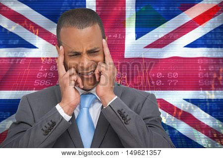 Stressed businessman putting his fingers on his temples against digitally generated uk national flag