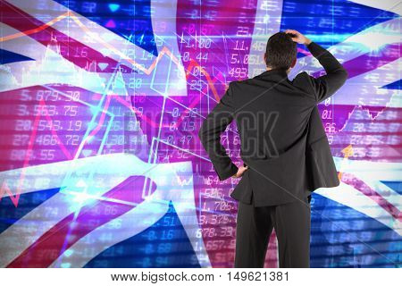 Businessman standing back to the camera with hand on head against digitally generated great britain national flag