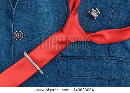 Red tie cufflinks and a tie clip lie on the denim jacket a top view