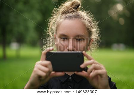 teenage girl taking photo with smartphone, in the park