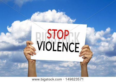 STOP VIOLENCE card in hand against blue sky with clouds. Selective focus.