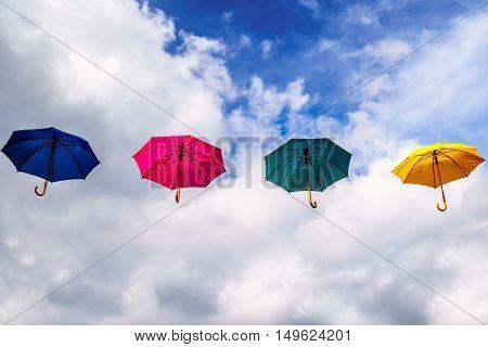 Blue Umbrella, Red Umbrella, Green Umbrella and Yellow Umbrella floating in the Air under Blue Sky and Clouds