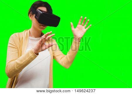 Businesswoman holding virtual glasses against green vignette