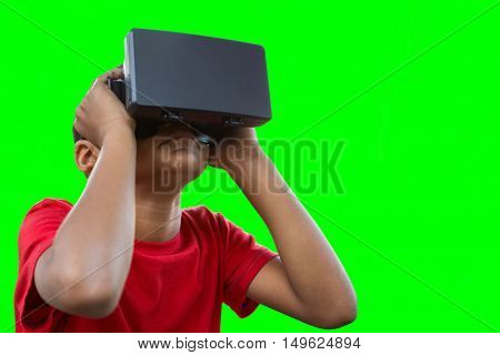 Boy with virtual reality simulator against green vignette