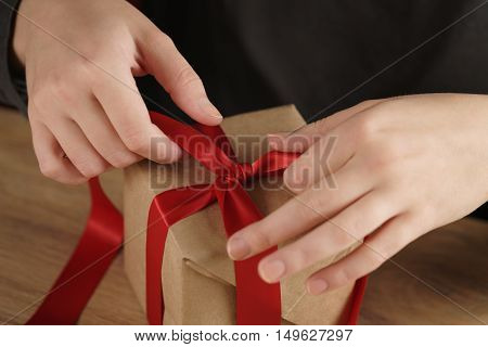 packing presents with red ribbon, craft paper box
