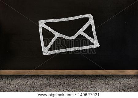 Black envelope drawing against blackboard on wall