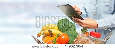 Woman with shopping cart and tablet computer.
