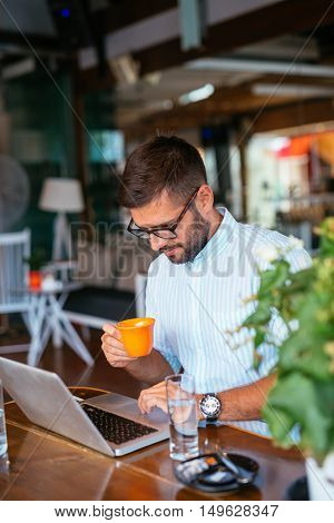 Handsome man working on a computer and drinking coffee in a cafe.